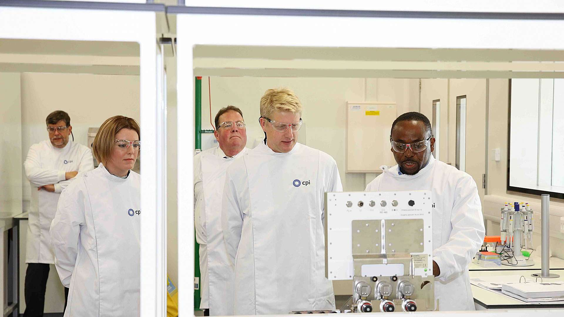 Photo of Jo Johnson getting a tour of the labs at the National Biologics Manufacturing Centre