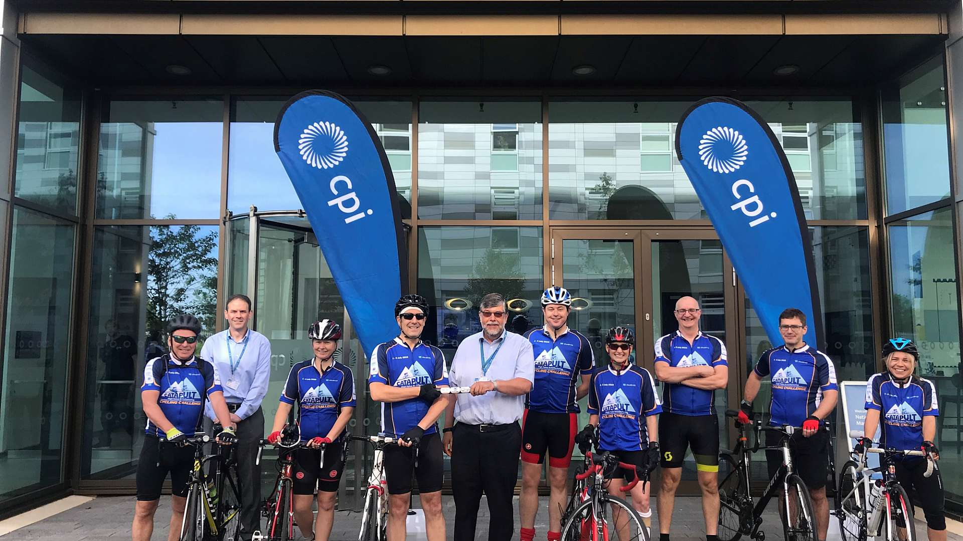 CPI cyclists with CPI's COO Frank Millar and CEO Nigel Perry receiving the baton which is being passed between all HVMC Centres on the route
