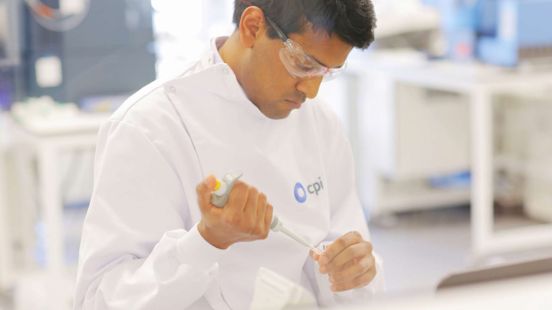 A photo of a CPI staff member using a pipette in a biological laboratory.