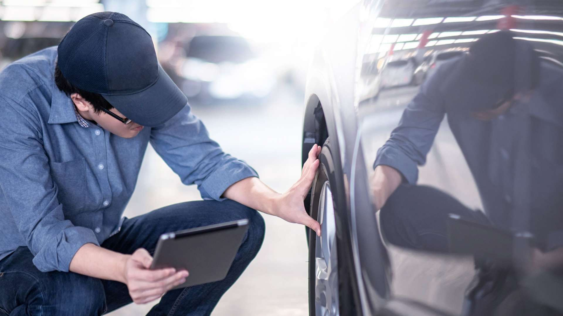 A photo of an electrical engineer checking a car's wheel
