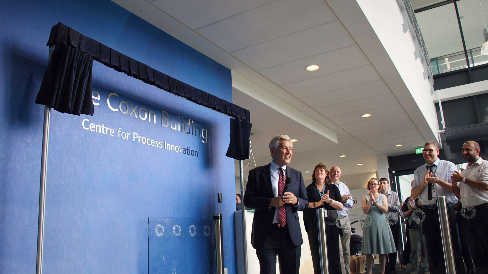 Bob Coxon unveils the wall plaque during CPI's naming ceremony