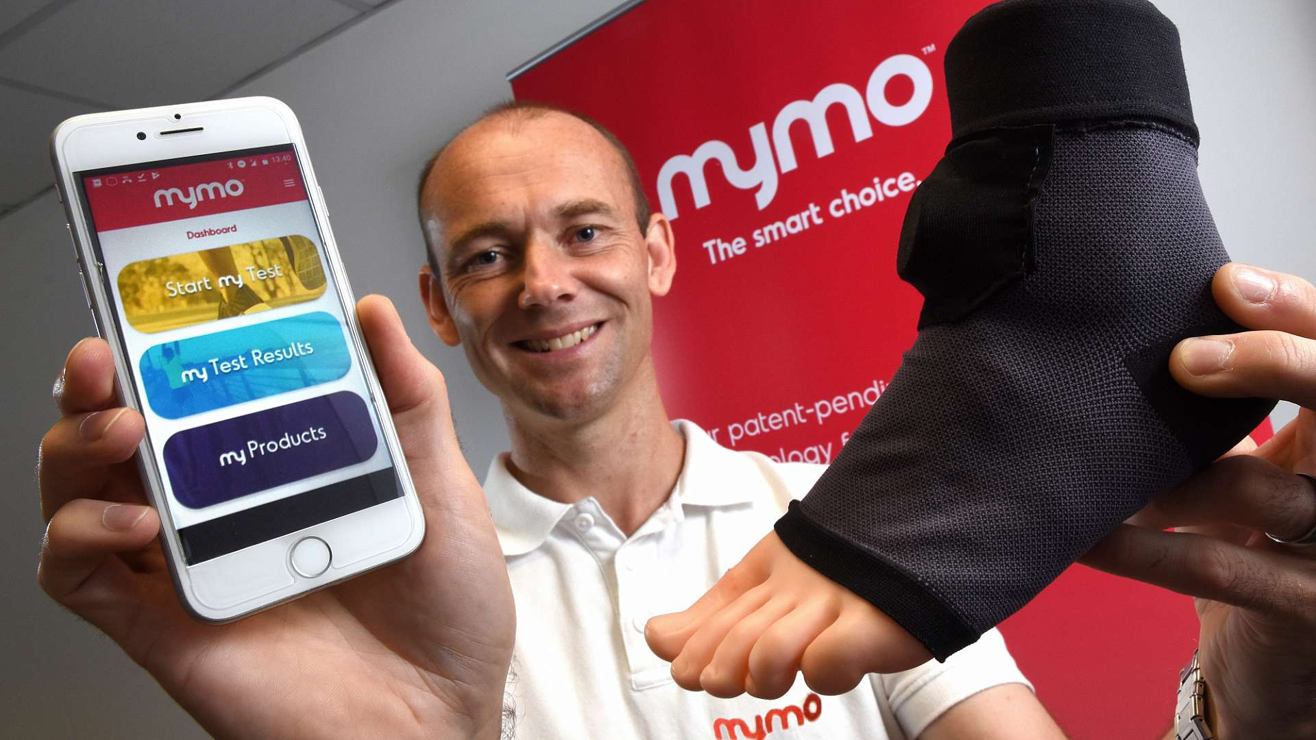Mr Downs is pictured with a wearable sock that uses artificial intelligence to monitor a runner's gait before sending the information to a smartphone