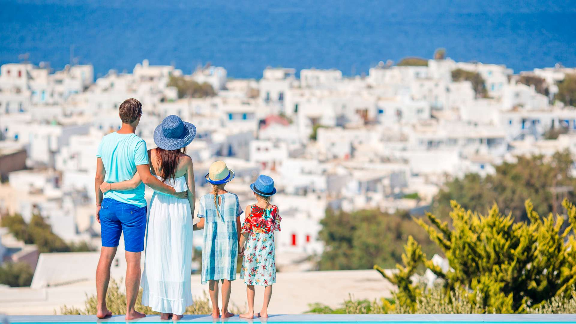A photo of a family on holiday in Europe stood by an infinite pool taking in the view