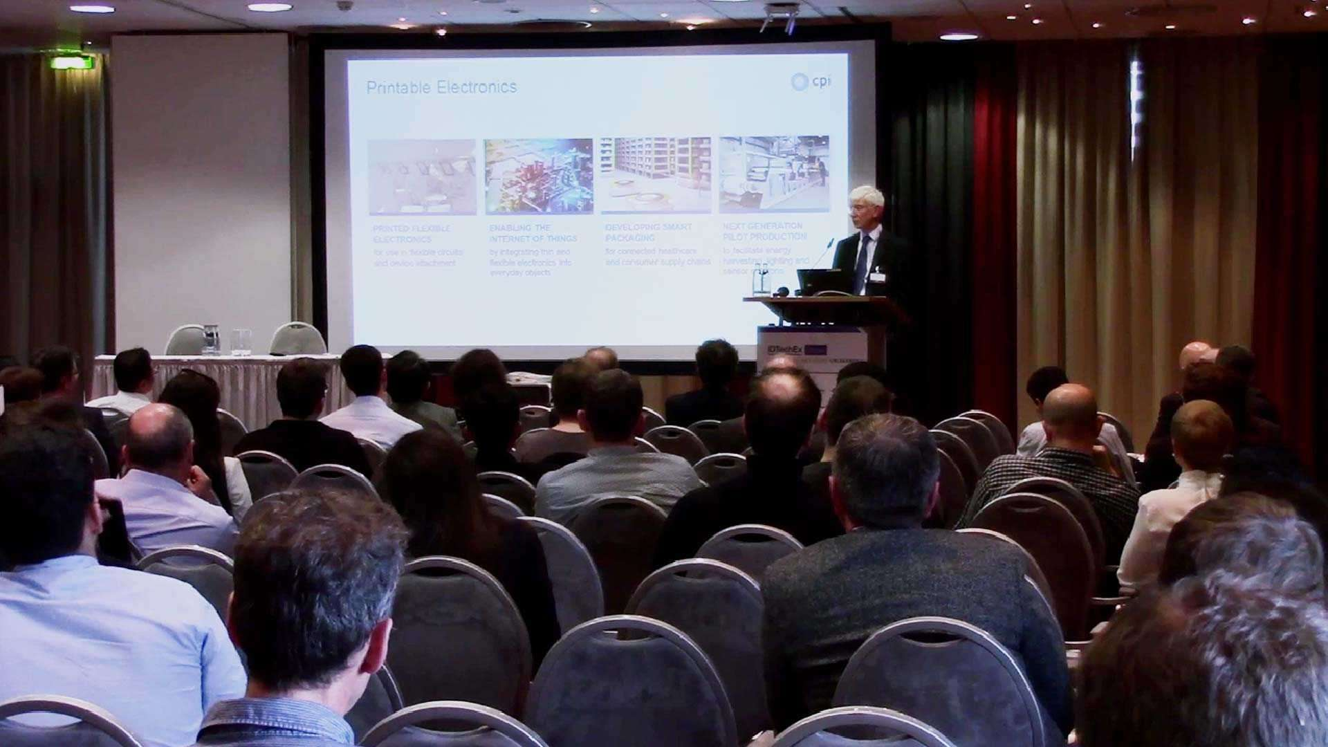 A photo Dr John Cocker, presenting to an audience of healthcare professionals and technology investors