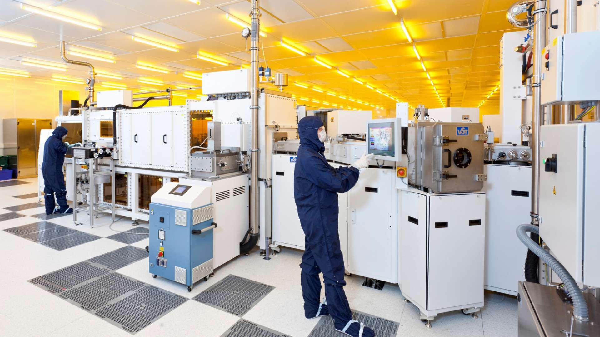 A photo of people working on large equipment in a CPI cleanroom