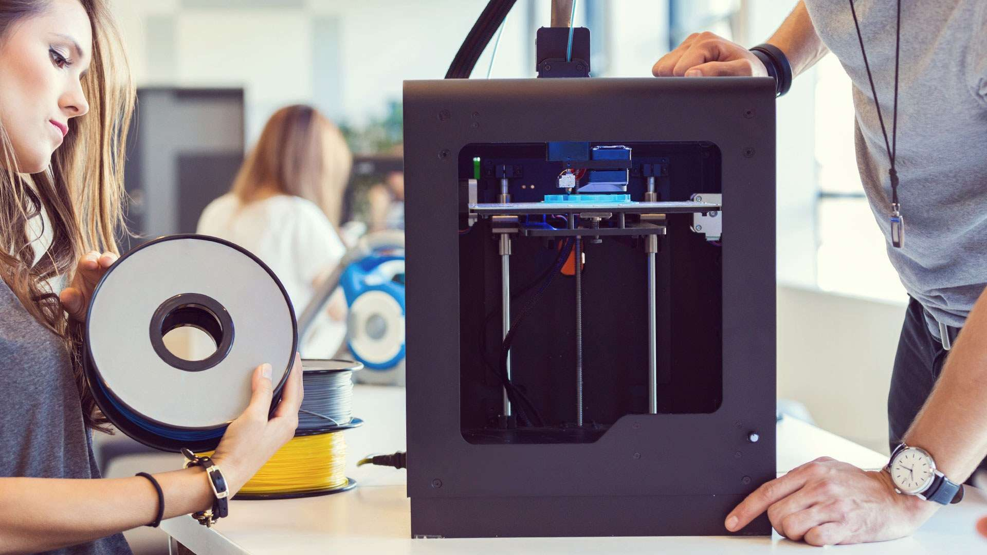 A photo of product designers using a 3D printer to create their concept