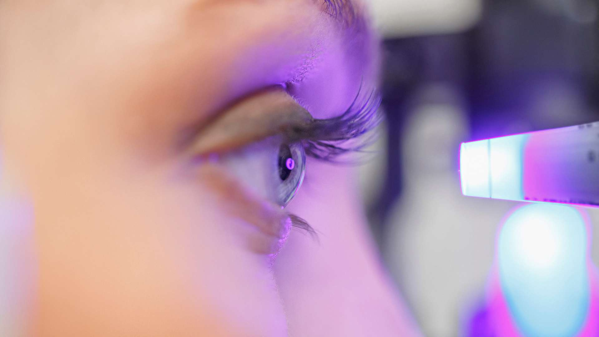 A photo of a person undergoing an eye examination with purple light