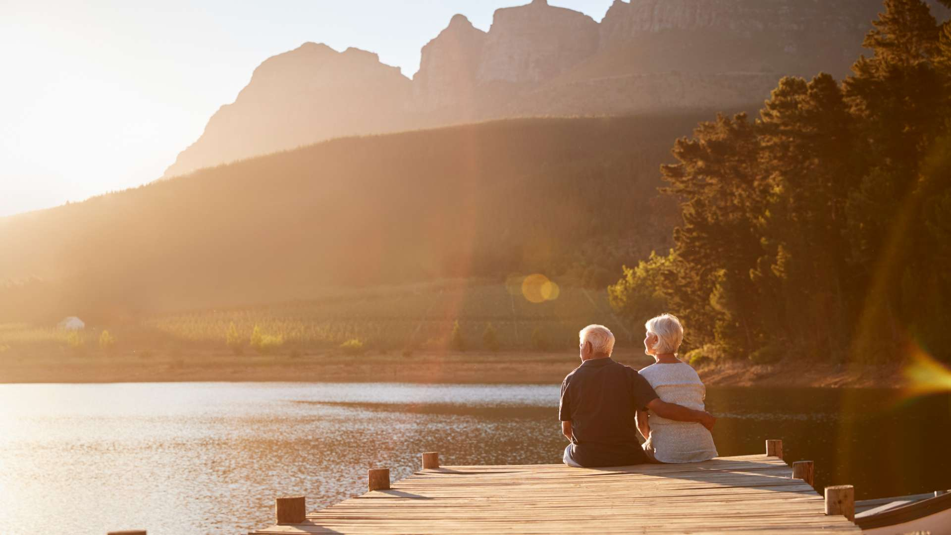 A photo of an elderly couple sat on the end of a jeti taking in view around them