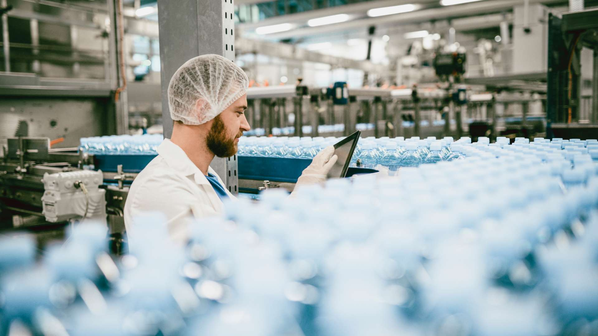 A photo of a man working in a packaging factory scanning finished products using a tablet device