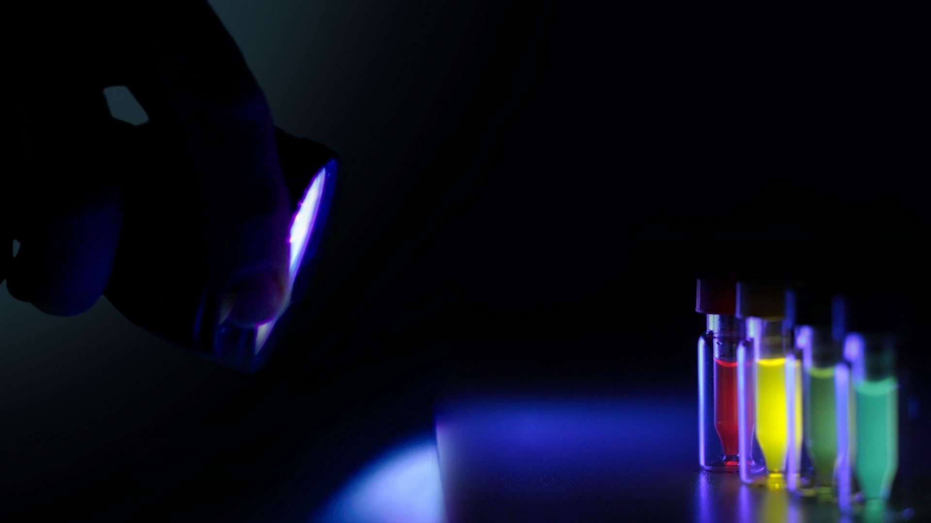 A photo of Stream Bio's product in vials, lit-up with a UV light