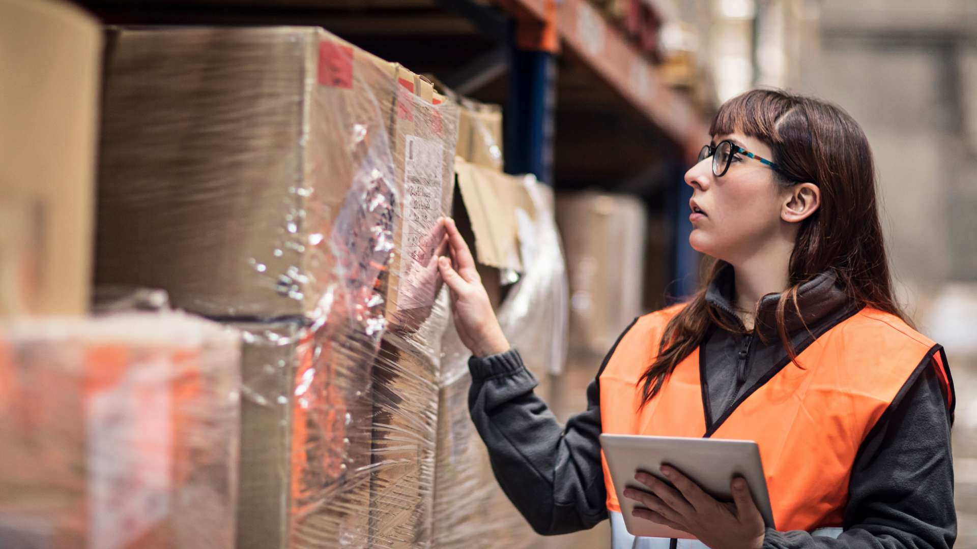 A photo of a woman in a distribution warehouse using a tablet device to track a package